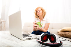 Young woman on the sofa with Gadgets. A young plus size woman sitting on the sofa with a Tablet PC and a Laptop on the Table Royalty Free Stock Photo