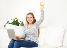 Young woman on a sofa is happy about her success Royalty Free Stock Photography