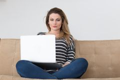 Young woman on sofa at home websurfing Stock Image