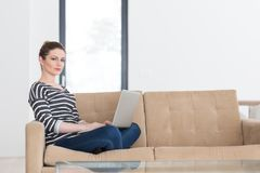 Young woman on sofa at home websurfing Royalty Free Stock Photography