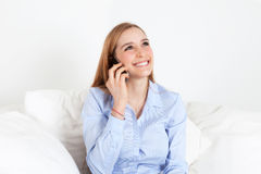 Young woman on a sofa laughing at phone Royalty Free Stock Images