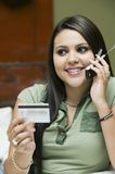 Young woman on sofa making purchase with credit card on mobile phone Royalty Free Stock Images