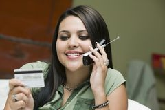 Young woman on sofa making purchase with credit card on mobile phone Stock Photo