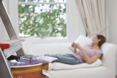 Young woman on sofa with mug, focus on paint pot and brush on ladder in foreground Stock Photos