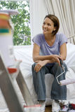 Young woman on sofa with paint roller, paint pot on ladder in foreground (differential focus). Young women on sofa with paint roller, paint pot on ladder in Stock Images