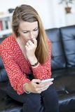 Young woman staring at her mobile phone and biting nails while sitting on a leather couch royalty free stock photography