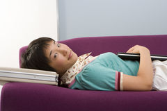Young woman on sofa using briefcase as pillow, portrait, close-up. Young women on sofa using briefcase as pillow, portrait, close-up Royalty Free Stock Images