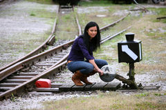 Young woman with soft about which direction. Woman with railway junction switch choosing direction Royalty Free Stock Photos
