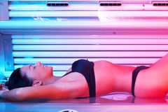 Young woman in solarium. Beautiful young woman tanning in solarium Stock Photography