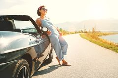 Young woman solo traveler stay near cabriolet car on picturesque. Mountain road Royalty Free Stock Photos