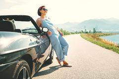Young woman solo traveler stay near cabriolet car on picturesque. Mountain road Royalty Free Stock Image
