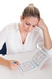 Young Woman Solving Sudoku Stock Photography