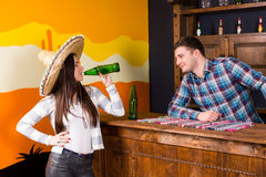 A young woman in a sombrero drinking a beer and standing at the. A young women in a sombrero drinking a beer and standing at the bar next to the bartender in a royalty free stock images