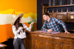 A young woman in a sombrero holding a beer and standing at the b. A young women in a sombrero holding a beer and standing at the bar next to the bartender in a royalty free stock image