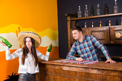 A young woman in a sombrero holding two bottles of beer and stan. A young women in a sombrero holding two bottles of beer and standing at the bar next to the royalty free stock image
