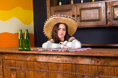 A young woman in a sombrero leaned on bar counter in Mexican pub. A young woman in a sombrero leaned on bar counter with beer bottles in Mexican pub royalty free stock photo