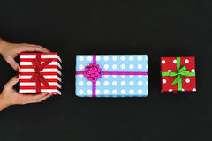 Young woman with some gifts. High-angle shot of a young caucasian woman with some gifts arranged in line on a dark gray surface, and wrapped in colorful papers Royalty Free Stock Photos