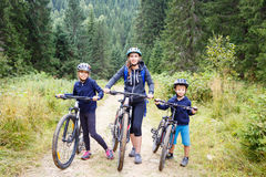 Young woman with son and daughter enjoying cycling Royalty Free Stock Images
