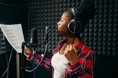 Young woman songs in audio recording studio royalty free stock image