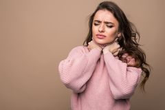 Young woman with sore throat isolated on brown background. Young pretty woman with sore throat isolated royalty free stock images