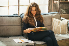 Young woman sorting letters in loft apartment. Young woman sorting letters in modern loft apartment Stock Photo