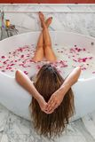 Young woman in spa enjoying bath with rose petals and relaxing.  stock images