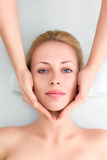 Young woman in spa gets a facial massage Royalty Free Stock Image