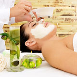Young woman at spa salon with cosmetic mask on face Stock Image