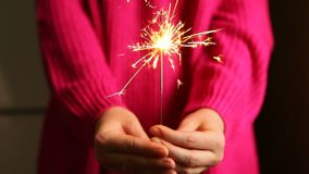 Young woman with sparkler or Bengal lights in hands, holidays concept. Young woman in pinkk clothing with sparkler or Bengal light in hands, holidays concept stock video