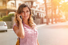 Young woman speaking on cell phone down the street Royalty Free Stock Photos