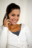 Young woman speaking on cellphone looking at you Royalty Free Stock Image