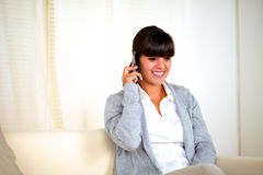 Young woman speaking at cellphone sitting on sofa Royalty Free Stock Images