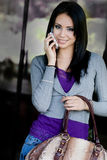 Young woman speaking on the mobile while shopping. Portrait of a cute young woman speaking on the mobile while holding gorgeous designer bag Royalty Free Stock Photography