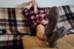 Young woman speaking by phone on couch in knitted socks Stock Image