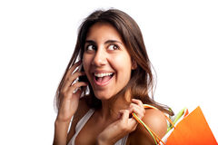 Young woman speaking on the phone. Young woman holding shopping bags and speaking on the phone Royalty Free Stock Image