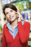 Young woman speaking on phone in shop Stock Photos
