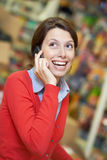 Young woman speaking on phone in shop Royalty Free Stock Images