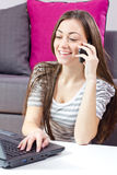 Young woman speaking by phone and using laptop Royalty Free Stock Images