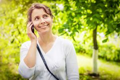 Young woman speaks by mobile phone in green park. Happy smiling girl is calling by phone on bright sunny spring day. Stock Photo