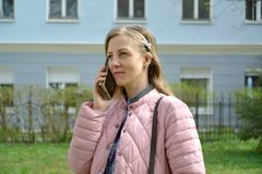 The young woman speaks by the mobile phone on the street.  stock images