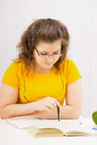 A young woman in spectacles is reading a book Royalty Free Stock Photography