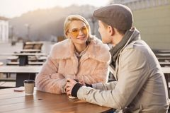 Young woman is spending time with her boyfriend. Amorous glance. Portrait of attractive girl in sunglasses is sitting at table with her boyfriend. She is looking Royalty Free Stock Photography