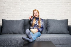 Young woman spends his free time watching TV on the couch at home, munching popcorn. Stock Image