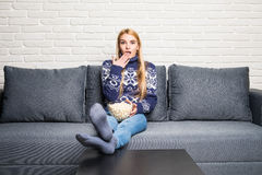Young woman spends his free time watching TV on the couch at home, munching popcorn. Royalty Free Stock Photos