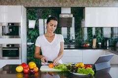 A young woman spends time at home, in the kitchen and in the roo. The young woman cuts vegetables in the kitchen with a knife and laptop on the table. Vegetable Royalty Free Stock Images