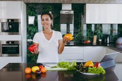 A young woman spends time at home, in the kitchen and in the roo. The young happy woman holding vegetables in hands in kitchen with laptop on the table Stock Photography