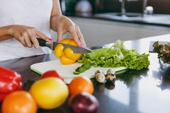 A young woman spends time at home, in the kitchen and in the roo. The young woman cuts vegetables in the kitchen with a knife. Healthy food - Vegetable salad Royalty Free Stock Photo