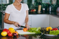 A young woman spends time at home, in the kitchen and in the roo. The young woman cuts vegetables in the kitchen with a knife. Healthy Food - Vegetable Salad Royalty Free Stock Photography
