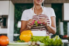 A young woman spends time at home, in the kitchen and in the roo. The young woman with headphones in the ears holding vegetables in hands in kitchen with laptop Stock Photography