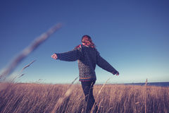 Young woman spinning around in meadow by the sea Royalty Free Stock Images